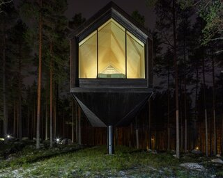 The gable-framed cabin hovers gently above the ground, blending in with the tall  trees.