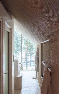 Upon entry, full-height glazing with a stunning view of the forested surroundings pulls you in, blurring the boundary between inside and outside. The cabin's utilitarian areas are located in the center of the plan, so the remainder of the space remains open.