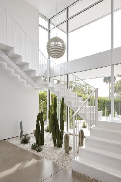 The Poul Henningsen pendant lights the stairwell. A cactus garden runs the length of the front yard and extends into the house.