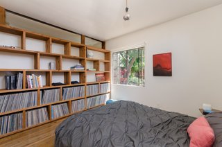 Bedroom with built-in wood shelves for records, etc.  Clerestory above to allow natural light into bathroom beyond.  Steel window with view to rear yard landscape.  Art by Peggy Hsu