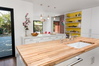 Kitchen at island with views of rear yard deck and dining room beyond