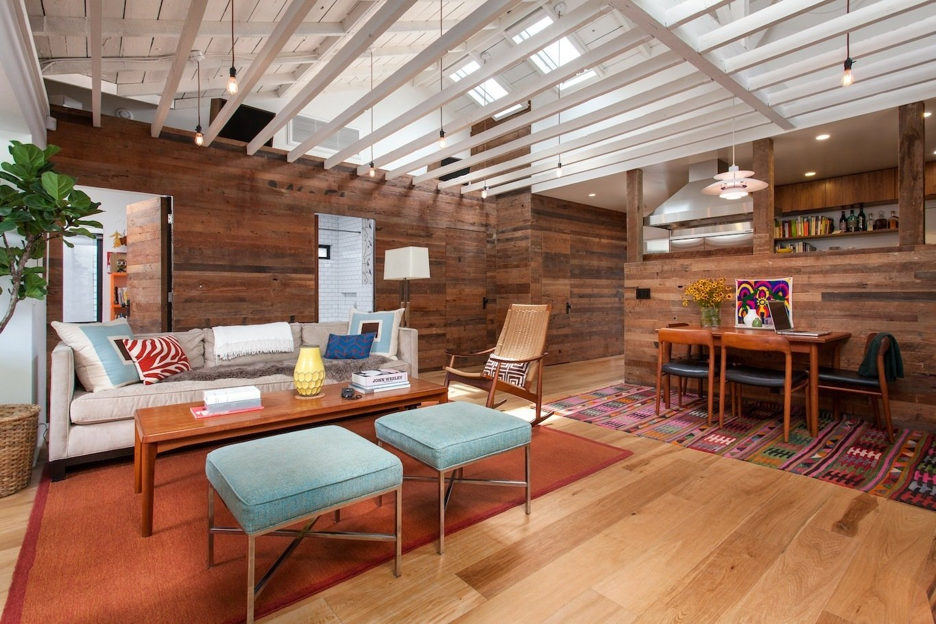 Chair, Sofa, Coffee Tables, Bench, Light Hardwood Floor, Ottomans, Pendant Lighting, Doors, Swing Door Type, Wood, and Interior Living Room looking East towards bedrooms and bathroom hidden behind reclaimed wood siding clad walls  Ashland Residence by Hsu McCullough