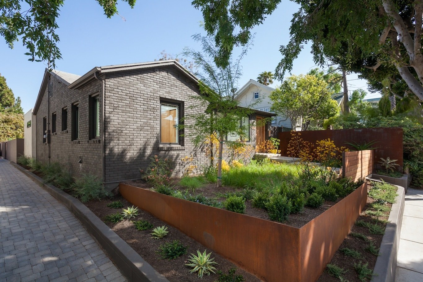 Outdoor, Front Yard, Garden, Side Yard, Trees, Grass, Hardscapes, Gardens, Raised Planters, Walkways, Wood Fences, Wall, Pavers Patio, Porch, Deck, Horizontal Fences, Wall, and Metal Fences, Wall Front yard entry at driveway apron with corten landscape walls and gate beyond  Ashland Residence by Hsu McCullough