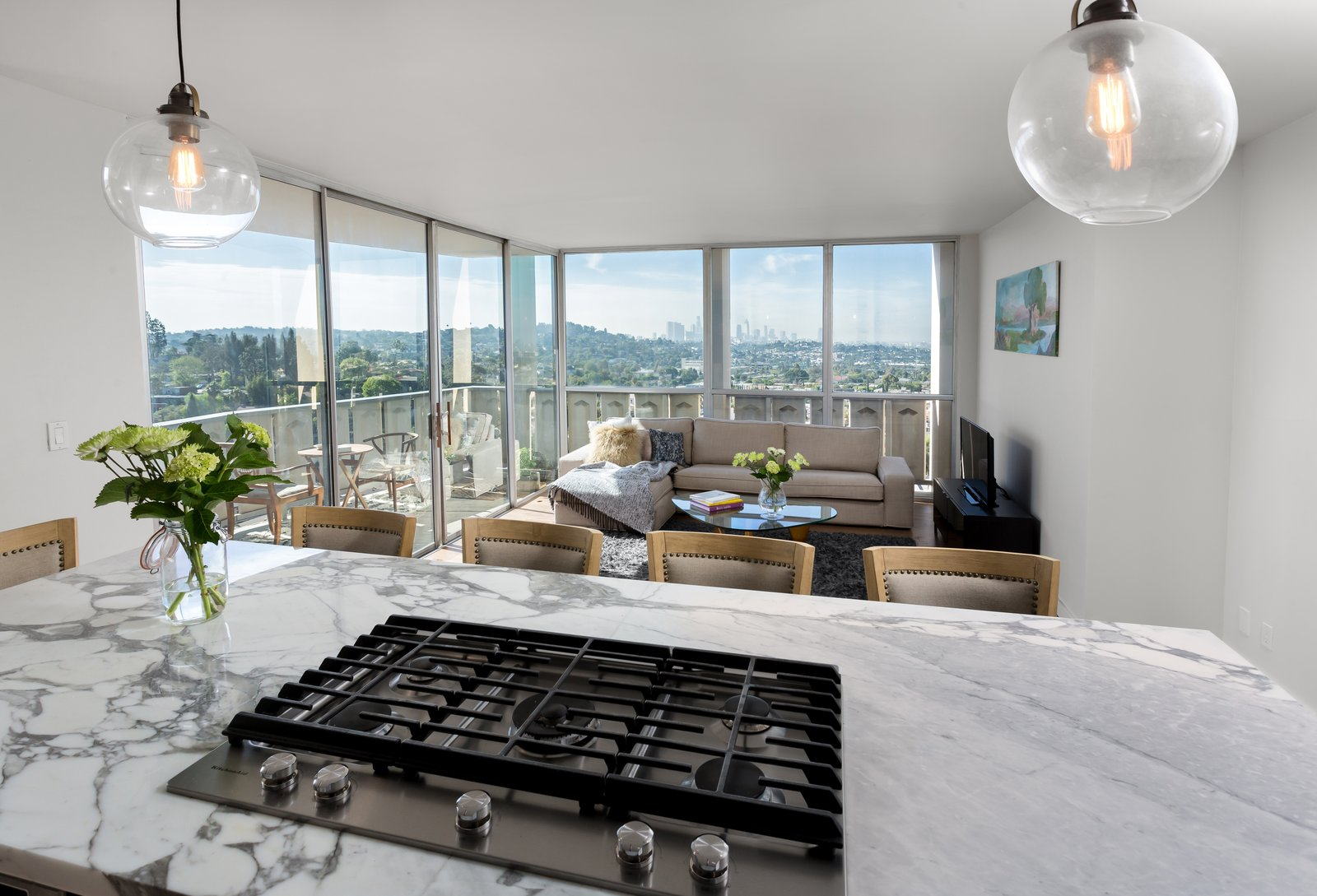 Sofa, Coffee Tables, Chair, Console Tables, Medium Hardwood Floor, Pendant Lighting, Metal, Windows, Exterior, Sliding Door Type, and Picture Window Type View of the city from the kitchen island   LFT Residence by Hsu McCullough