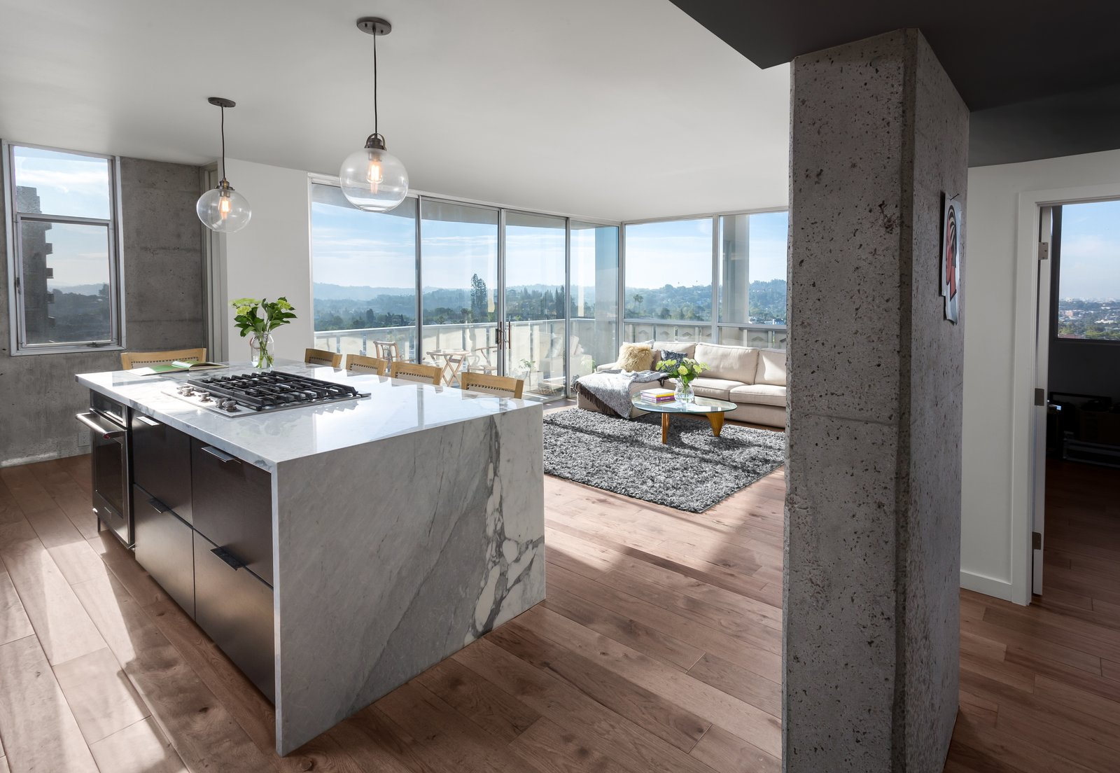 Kitchen, Marble, Wood, Marble, Medium Hardwood, Pendant, Refrigerator, Wall Oven, Cooktops, Dishwasher, and Undermount Kitchen island, Living Room and Study from entry with panoramic views of Los Angeles beyond  Best Kitchen Cooktops Marble Medium Hardwood Marble Photos from LFT Residence