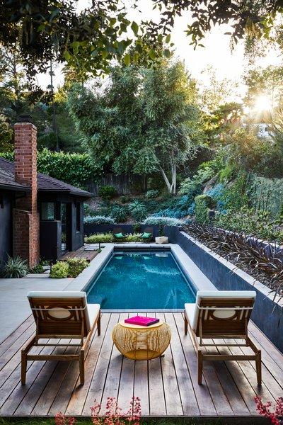 The lounge deck at the rear yard of Sunset Hills Residence features a swimming pool surrounded by lush gardens. Architect Hsu McCullough's design beautifully merges minimalism with an abundance of nature.