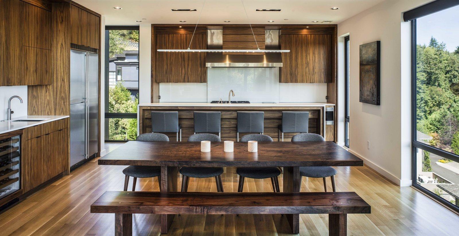 Kitchen, Wood Cabinet, Refrigerator, Medium Hardwood Floor, Ceiling Lighting, Pendant Lighting, Undermount Sink, and Range Kitchen  Music Box Residence by Scott | Edwards Architecture