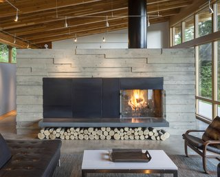 After discovering their client's love for the ritual of making campfires, the team behind Scott | Edward Architecture created a double-sided, concrete fireplace, which essentially separates the public and private spaces of the home.