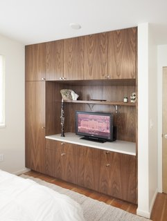 Since the closet wasn't being used for much hanging storage anyway, we created a more functional solution for that area using more custom built-ins. Now they have a great place to store what they need to store, while still having a smaller hanging area on the left.