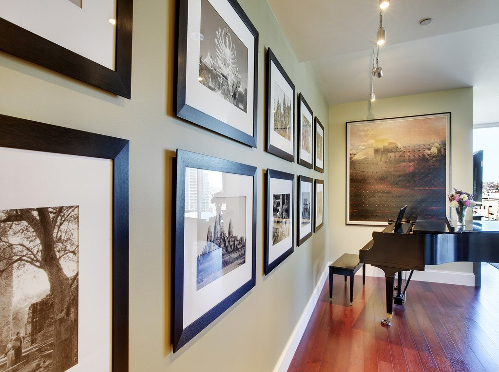 Hallway and Medium Hardwood Floor John is an avid world traveler and photographer. He took these photos (left) on one of his journeys to Thailand. We had them framed and hung in this bold arrangement. The Galen Garwood painting at the end of the hall was from their previous home. Originally, its frame was painted a light mauve, reminiscent of the 80s, so we chose to re-paint the frame an espresso/black. The small change brought the whole piece up-to-date.  Downsize Upstyle