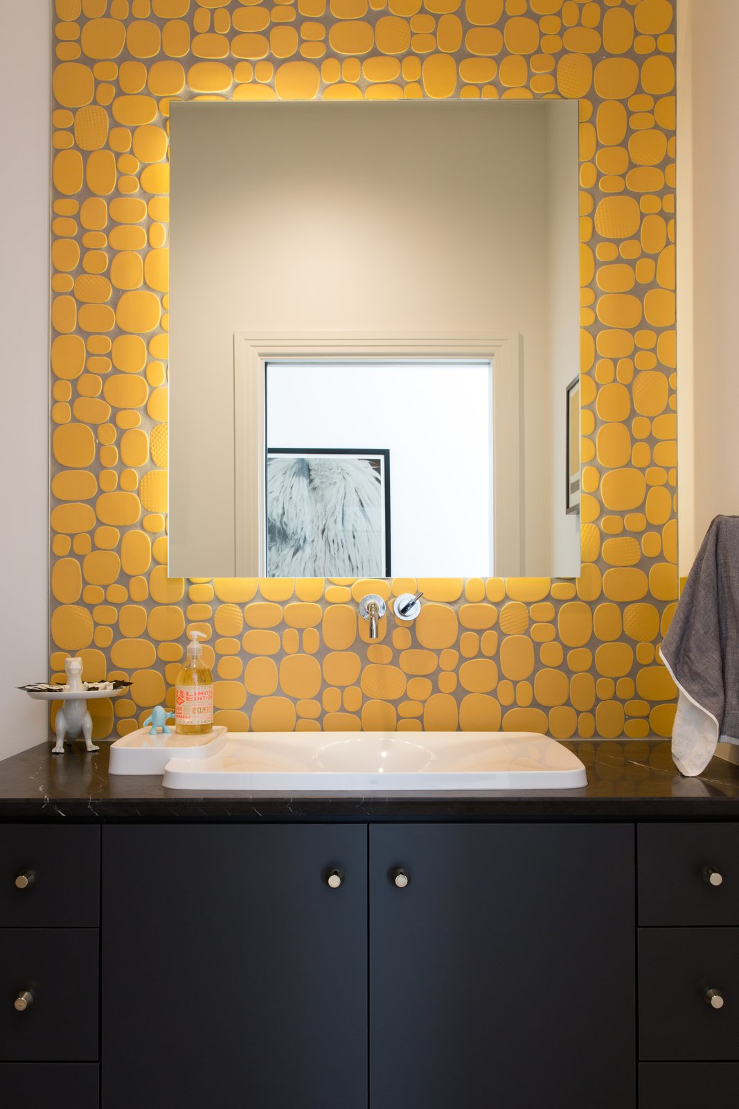 Bath Room, Ceramic Tile Floor, Marble Counter, Drop In Sink, Drop In Tub, Enclosed Shower, and Ceiling Lighting The North bathroom features Rex Rox Studio solar yellow ceramic tile by Modwalls, a custom vanity, marble countertop with knife-edge detail, and Axor Bouroullec faucets.  Signature Trustile Doors & Emtek Hardware exemplify the finish detail throughout the property.  1980s Modern Meets The New Millennium