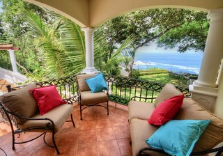 Covered terrace overlooking pool, garden, ocean
