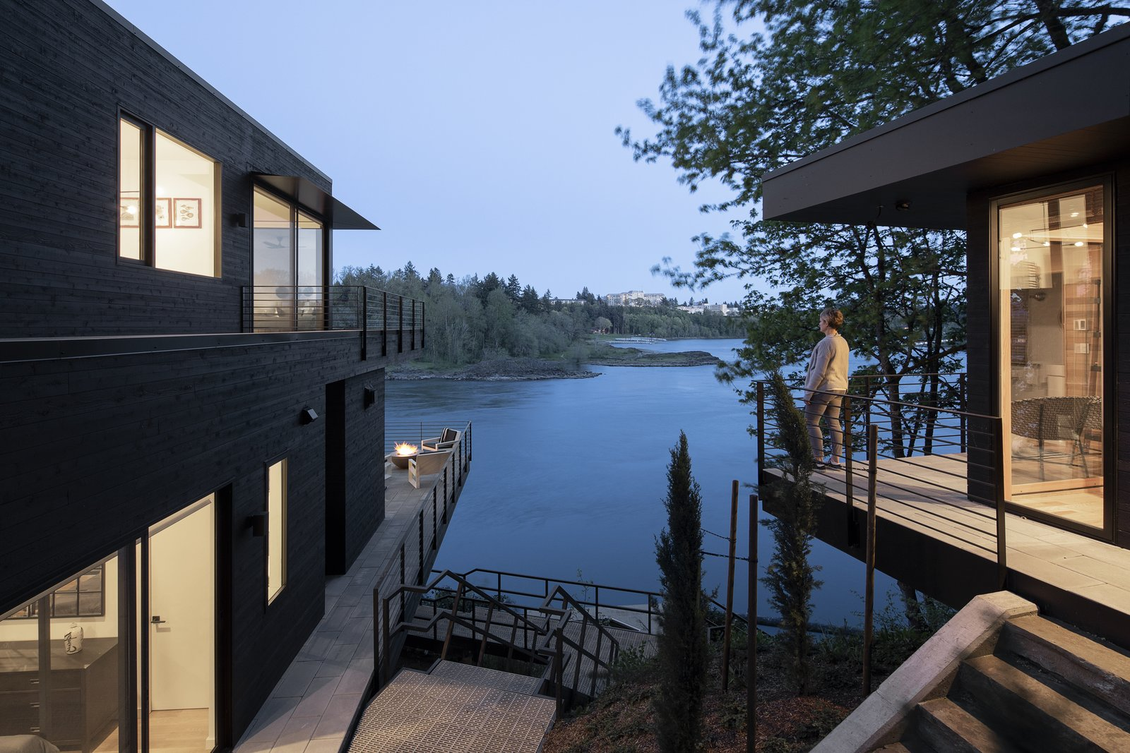 To the right is the small guest cabin perched on the cliff. To the left is the main house cantilevered over the river.  Riverwood