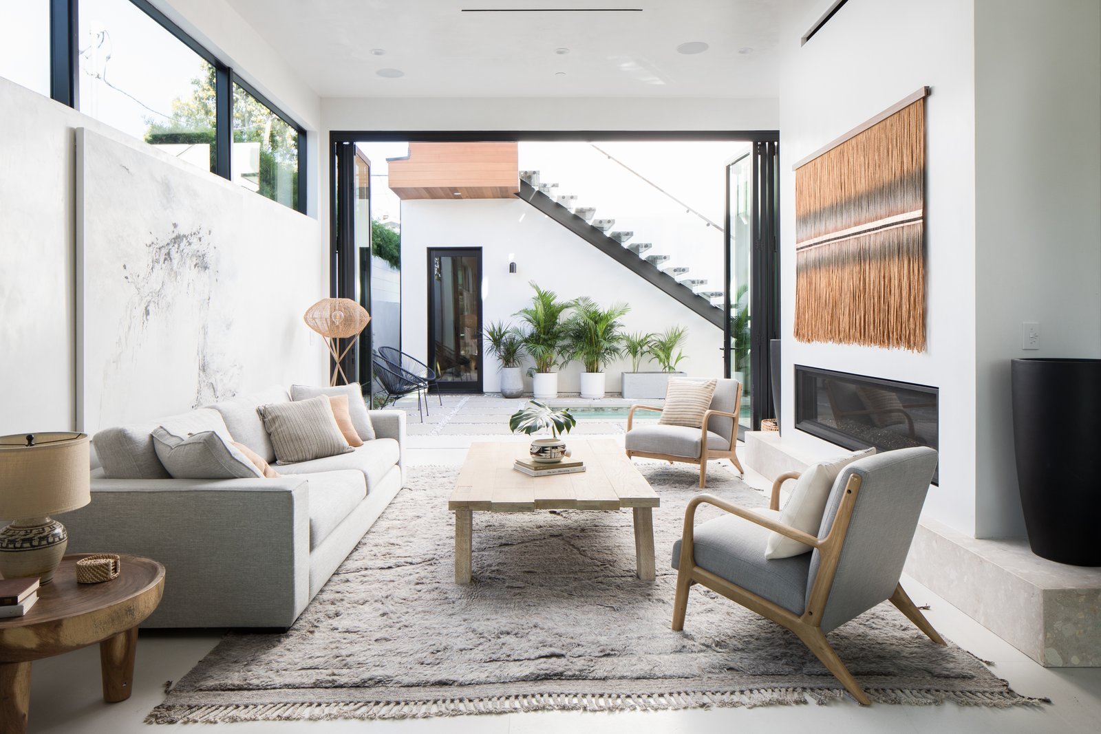 Living Room, Sofa, Recessed Lighting, Gas Burning Fireplace, Porcelain Tile Floor, Coffee Tables, Lamps, End Tables, and Chair The home's open design is perfect for indoor/outdoor living.   Milwood Residence by Mayes Office