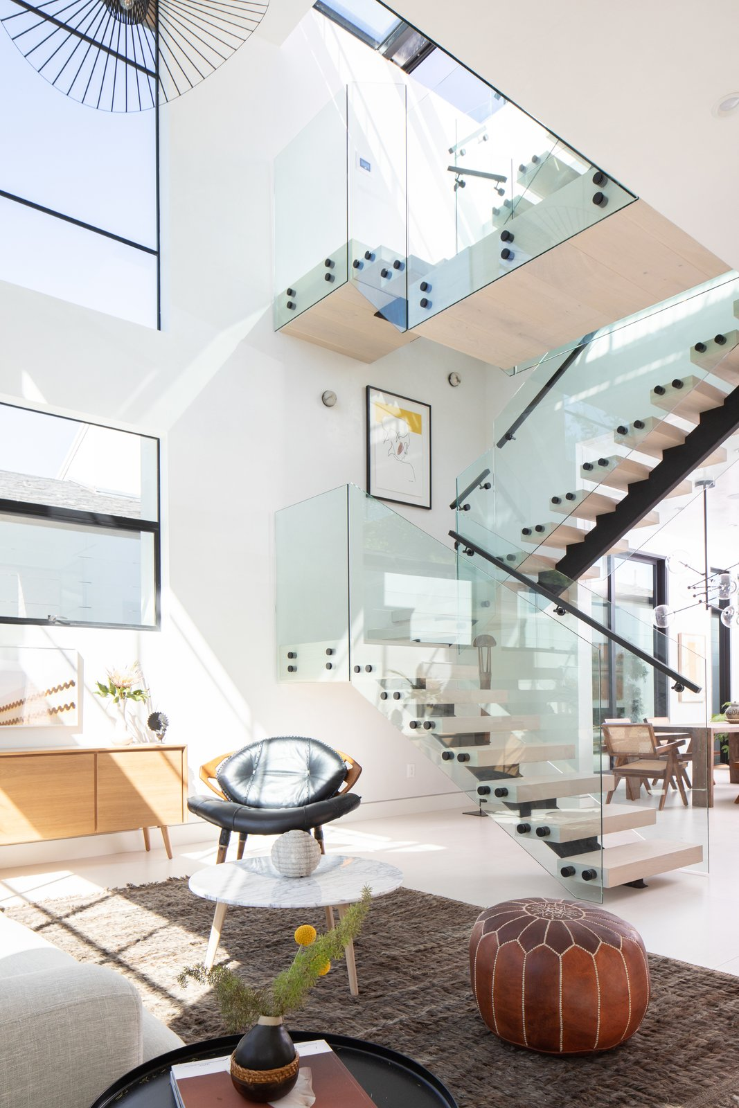 Staircase, Glass Railing, Metal Railing, and Wood Tread Natural light illuminates living area.   Milwood Residence by Mayes Office