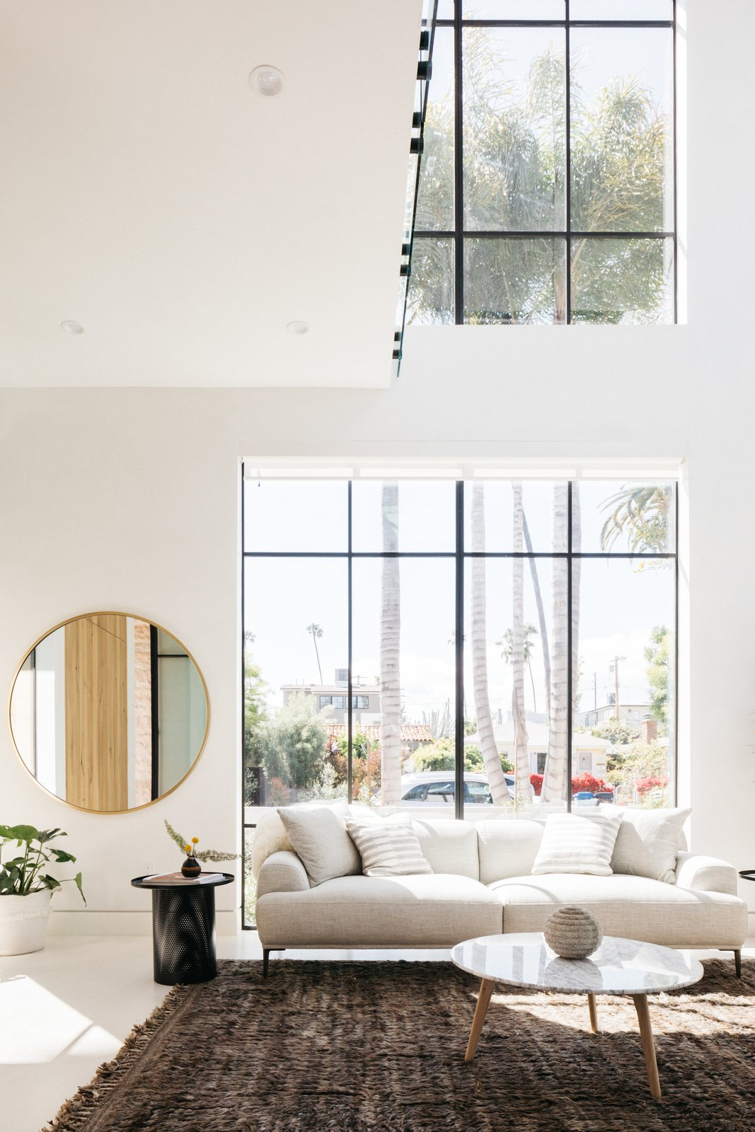 Living Room, Ceiling Lighting, Concrete Floor, Recessed Lighting, Coffee Tables, Sectional, and Rug Floor The main entrance of the house leads into the open living space, which hosts the living room, dining area, and kitchen.  Milwood Residence by Mayes Office