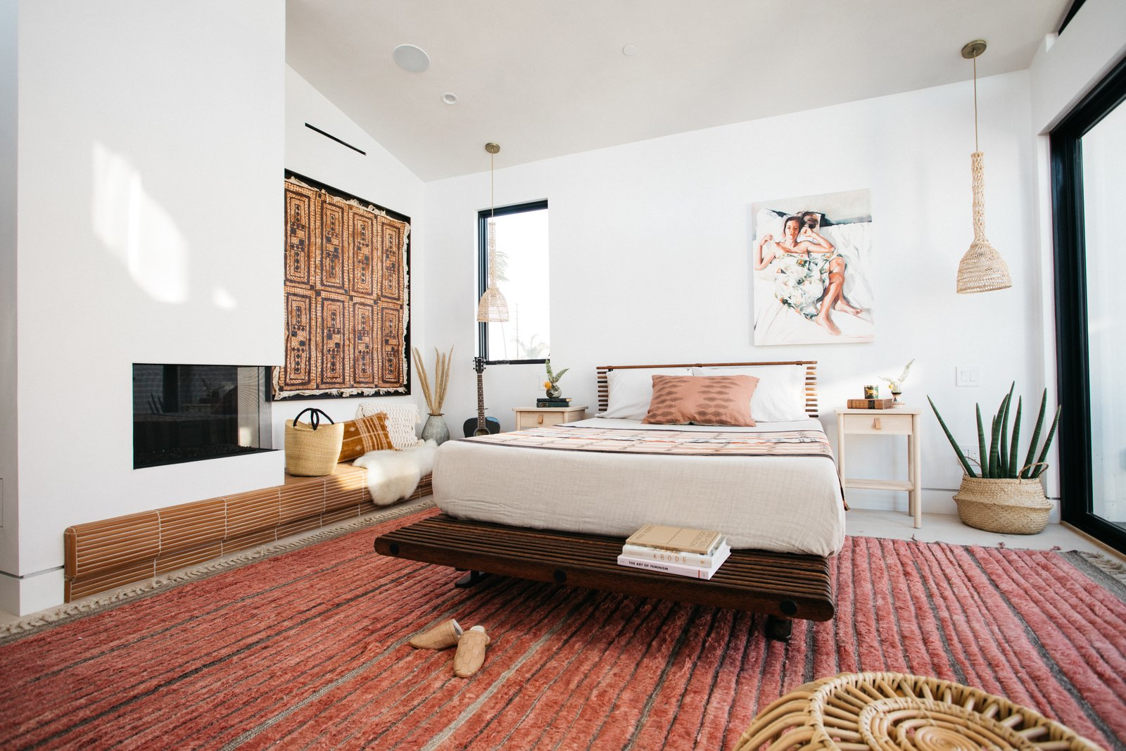 Bedroom, Rug Floor, Night Stands, Porcelain Tile Floor, Recessed Lighting, Pendant Lighting, Bed, and Terra-cotta Tile Floor Fireplace in the master bedroom offers a cozy respite for its occupants during winter.   Milwood Residence by Mayes Office