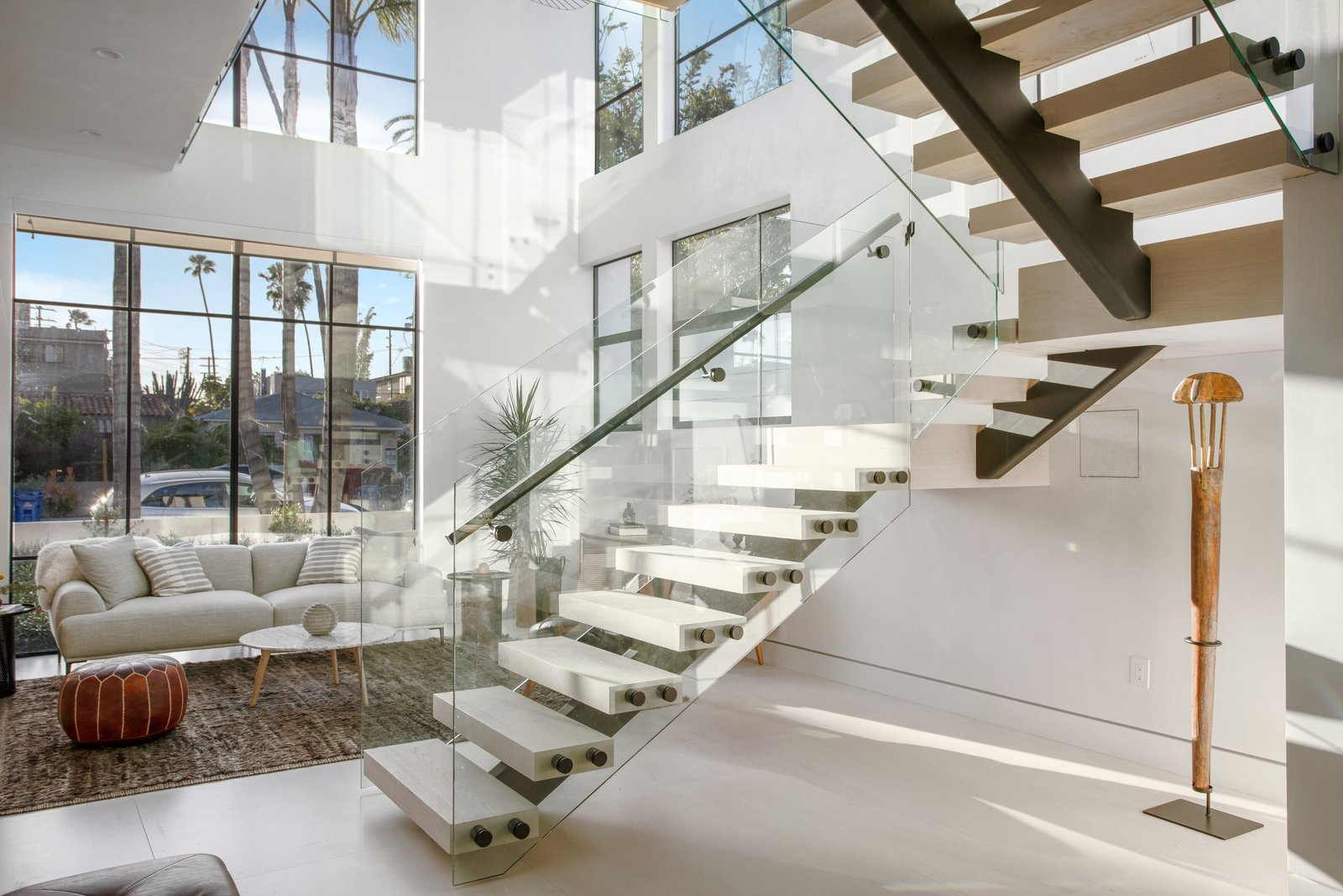 Staircase, Wood Railing, Wood Tread, and Glass Railing High ceilings brings natural light and views into the space.   Milwood Residence by Mayes Office