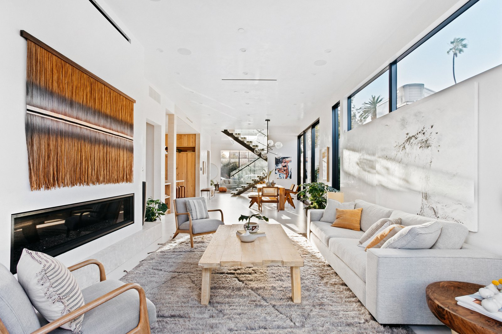 Living Room, Recessed Lighting, Coffee Tables, Chair, Porcelain Tile Floor, Sofa, and Gas Burning Fireplace The open floor plan which blends living and dining spaces makes the home ideal for family or friendly gatherings.   Milwood Residence by Mayes Office