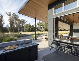 Generously shady roof overhangs provide shelter from the summer heat and oversized doors allow air to move through.