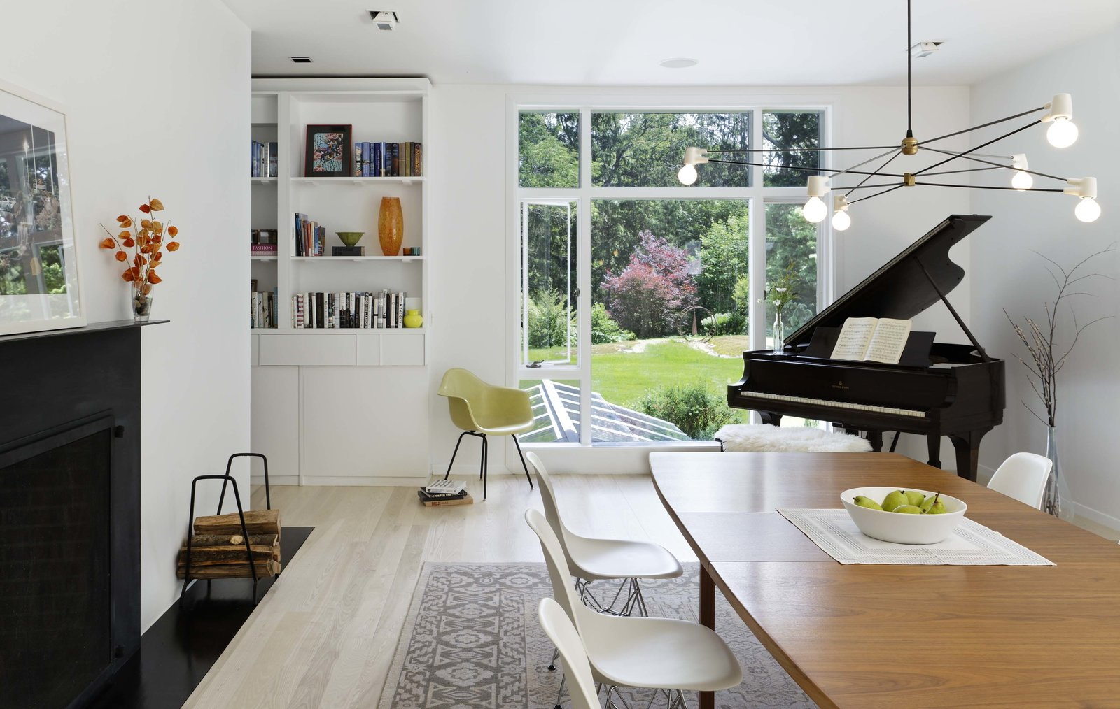 """Dining Room, Chair, Shelves, Table, Standard Layout Fireplace, and Pendant Lighting The """"sculptural"""" kitchen was replaced with a new open-plan cooking space, where concrete countertops are paired with glossy white cabinets and large windows frame views of the landscape.  Modern Barns by Aamodt / Plumb"""