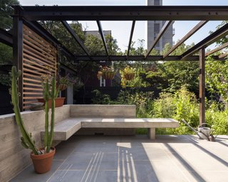 The combination of a low concrete wall and built-in bench creates an intimate seating area that acts as an extension to the kitchen and dining room. Another steel trellis above creates an armature for more plants that will fill in and provide shade. The terrace is topped with blue stone and wood screens give the plants a ladder on which to grow.