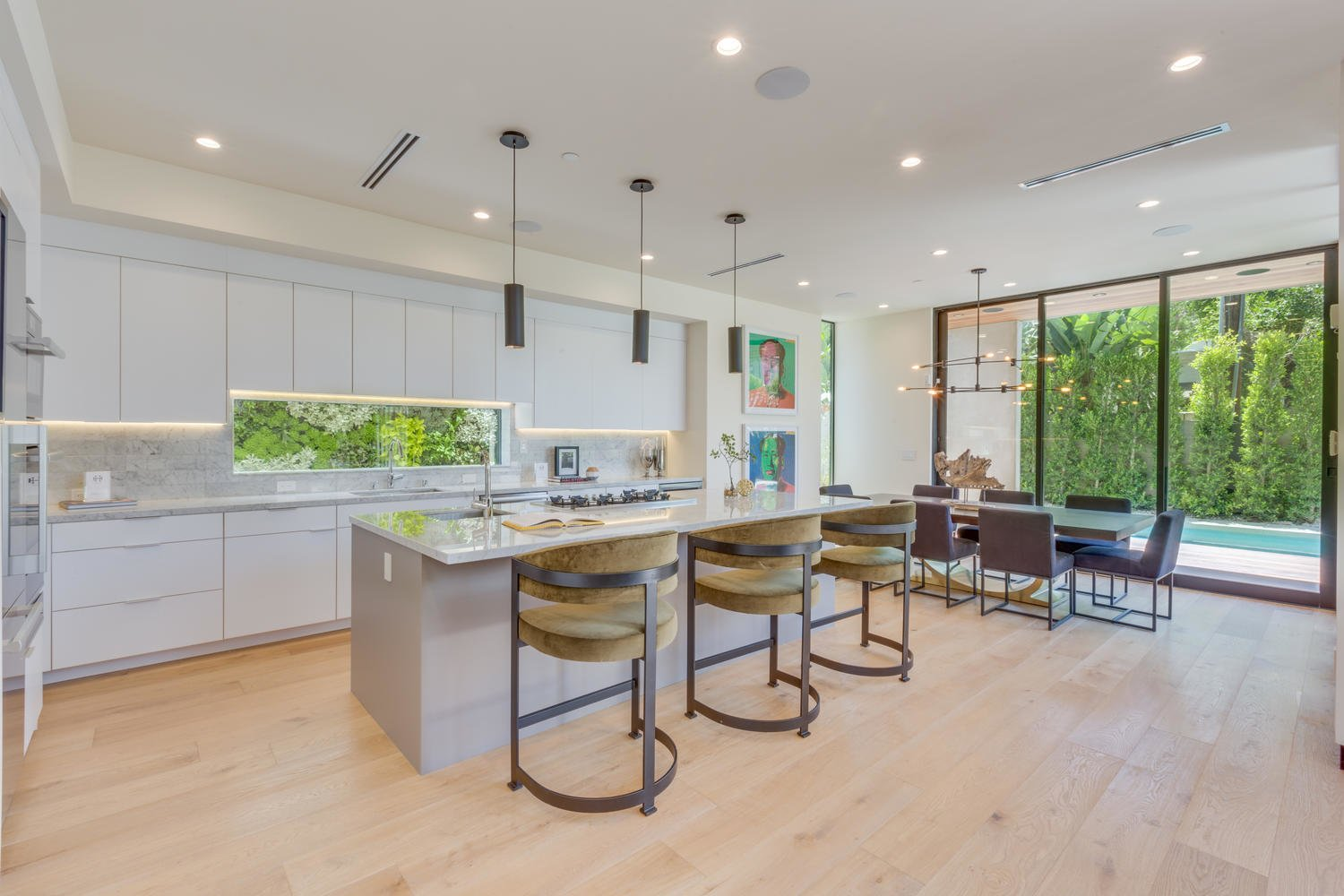 Kitchen, Marble Counter, White Cabinet, Marble Backsplashe, Light Hardwood Floor, Ceiling Lighting, Accent Lighting, Pendant Lighting, Recessed Lighting, Refrigerator, Wall Oven, Dishwasher, Microwave, Ice Maker, Cooktops, Wine Cooler, and Drop In Sink Kitchen/Dining Area  The Rosewood Residence