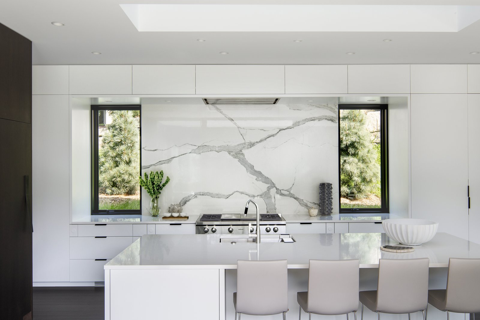 Built on a hilly, South-facing site populated with mature heritage trees in an established neighborhood, this home finds its sophisticated form through the traditional motifs. The highly linear, open floor plan is adorned with chic finishes, including a sleek wall of custom cabinetry.   Tagged: Kitchen, Engineered Quartz, White, Dark Hardwood, Stone Slab, Range, Undermount, Wall Oven, and Recessed.  Best Kitchen Engineered Quartz Undermount Photos from Huntington Residence