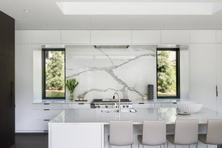The use of both black and white kitchen cabinets is a unique design choice for black and white kitchens, but it works well in this lovely kitchen, a study in dark and light. It incorporates a fantastic black-and-white marble backsplash, which brings together the kitchen's many other elements, like dark hardwood floors and a white quartz countertop.