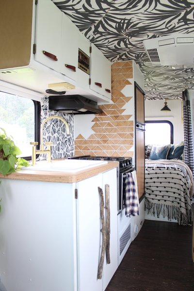 While technically a little later than midcentury, and certainly not a traditional home, this renovation of a 1980s RV by a Portland couple took advantage of the potential beyond the dingy wood laminate cabinets and the dirty beige carpet that was consuming the floor. Owner Liz Kamarul envisioned how she could transform it, imagining white cupboards, interesting wallpaper for the ceiling, and texture introduced by textiles.