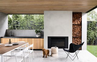 """""""A large loggia adjacent to the pool includes an outdoor kitchen and open fireplace. Timeless external finishes include cement render walls, metal fascias and timber soffits, and contrasting black powder-coated door frames and screens,"""" says the architect and interior designer, InForm."""