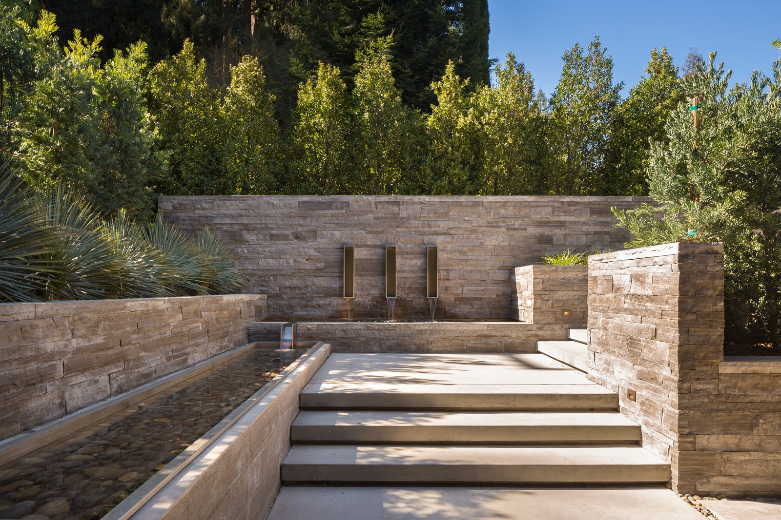 Entry walkway has stacked limestone walls  and linear water features.  Ross Modern