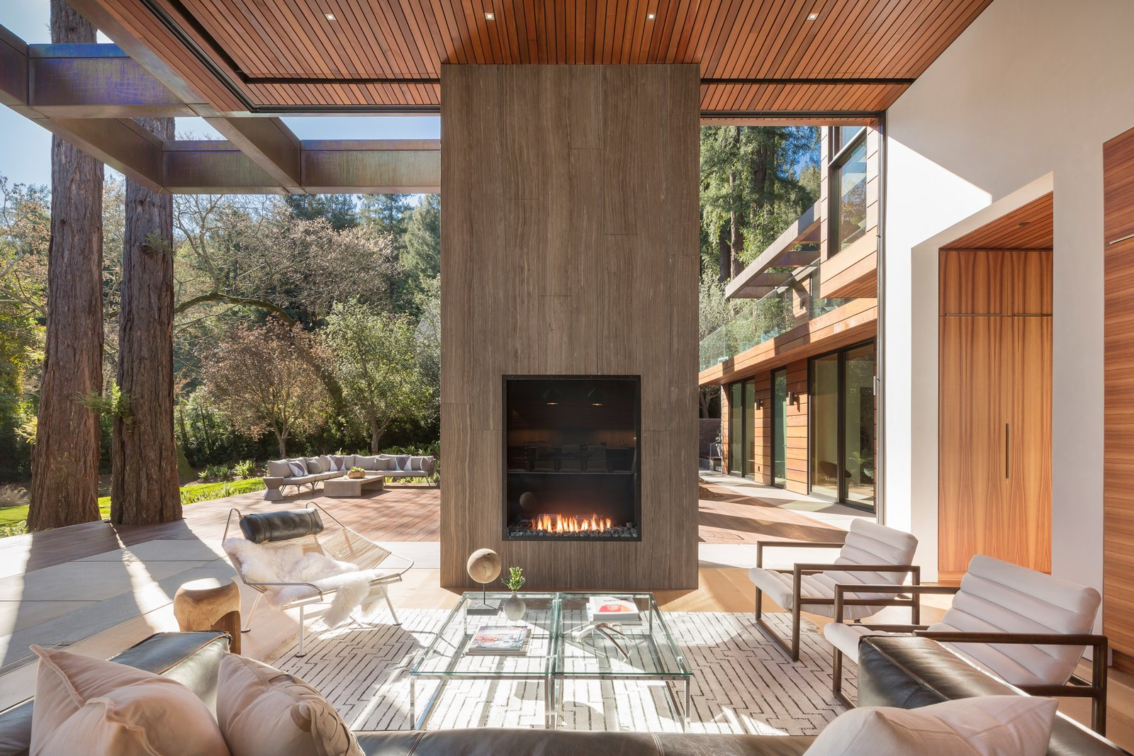 Living, Sofa, Two-Sided, Ceiling, Gas Burning, Chair, and Light Hardwood Limestone wrapped monolithic wall with fireplaces on both sides  Best Living Two-Sided Sofa Photos
