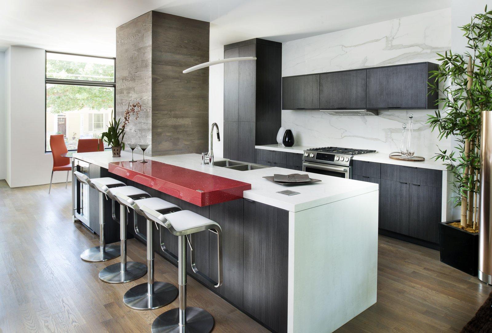 Kitchen, Quartzite Counter, Engineered Quartz Counter, Laminate Cabinet, Medium Hardwood Floor, Stone Slab Backsplashe, Pendant Lighting, Range, Range Hood, and Undermount Sink Kitchen Island  Photos from Sanders