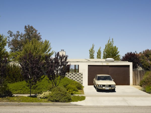 At a home designed by Escher GuneWardena Architecture in Los Angeles, California, the two-door garage has minimally-detailed doors in a darker color that slide horizontally, instead of rolling up or hinging inward.