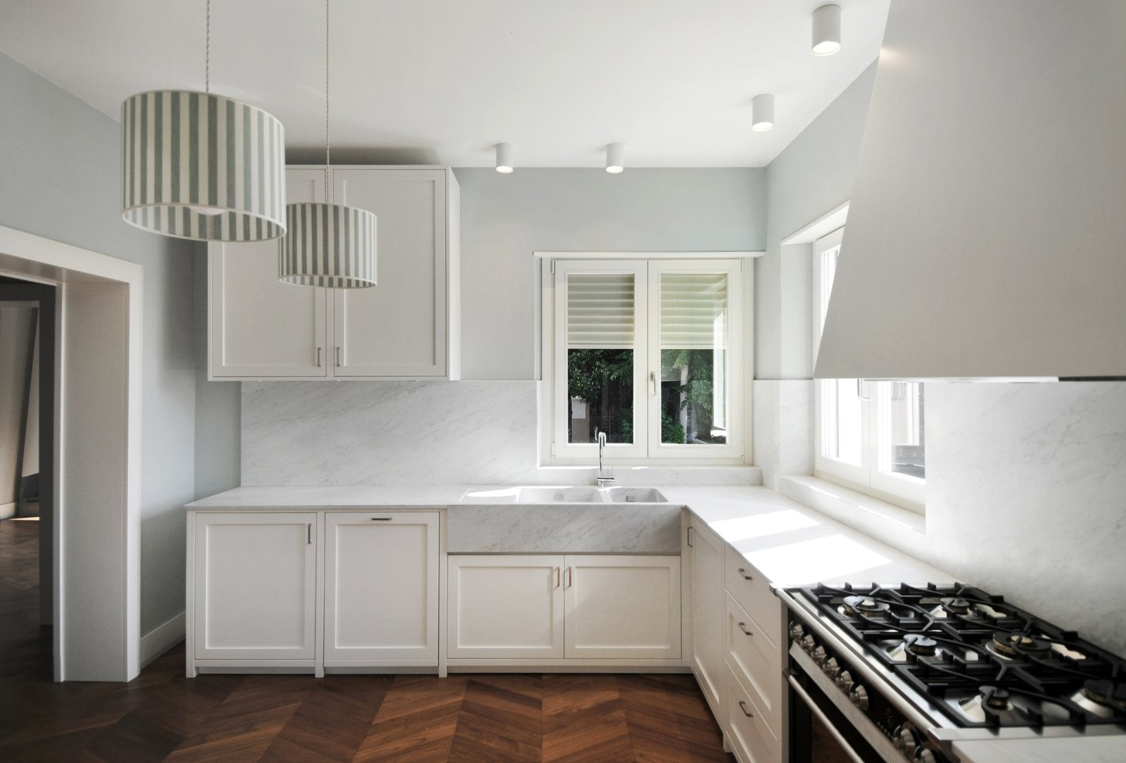 Kitchen, White Cabinet, Medium Hardwood Floor, Marble Backsplashe, Marble Counter, Ceiling Lighting, Drop In Sink, Dishwasher, and Refrigerator buda_kitchen  Best Photos from buda