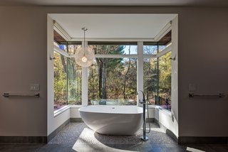 The Bentleyville Residence's bathroom features large windows and folding doors that provide expansive views of the surrounding woodland.