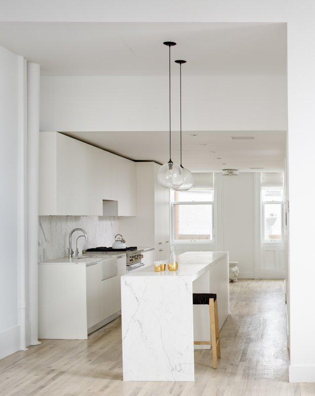 Kitchen, Marble Counter, Light Hardwood Floor, White Cabinet, Stone Tile Backsplashe, Pendant Lighting, Recessed Lighting, and Drop In Sink Kitchen  Grand St. Residence