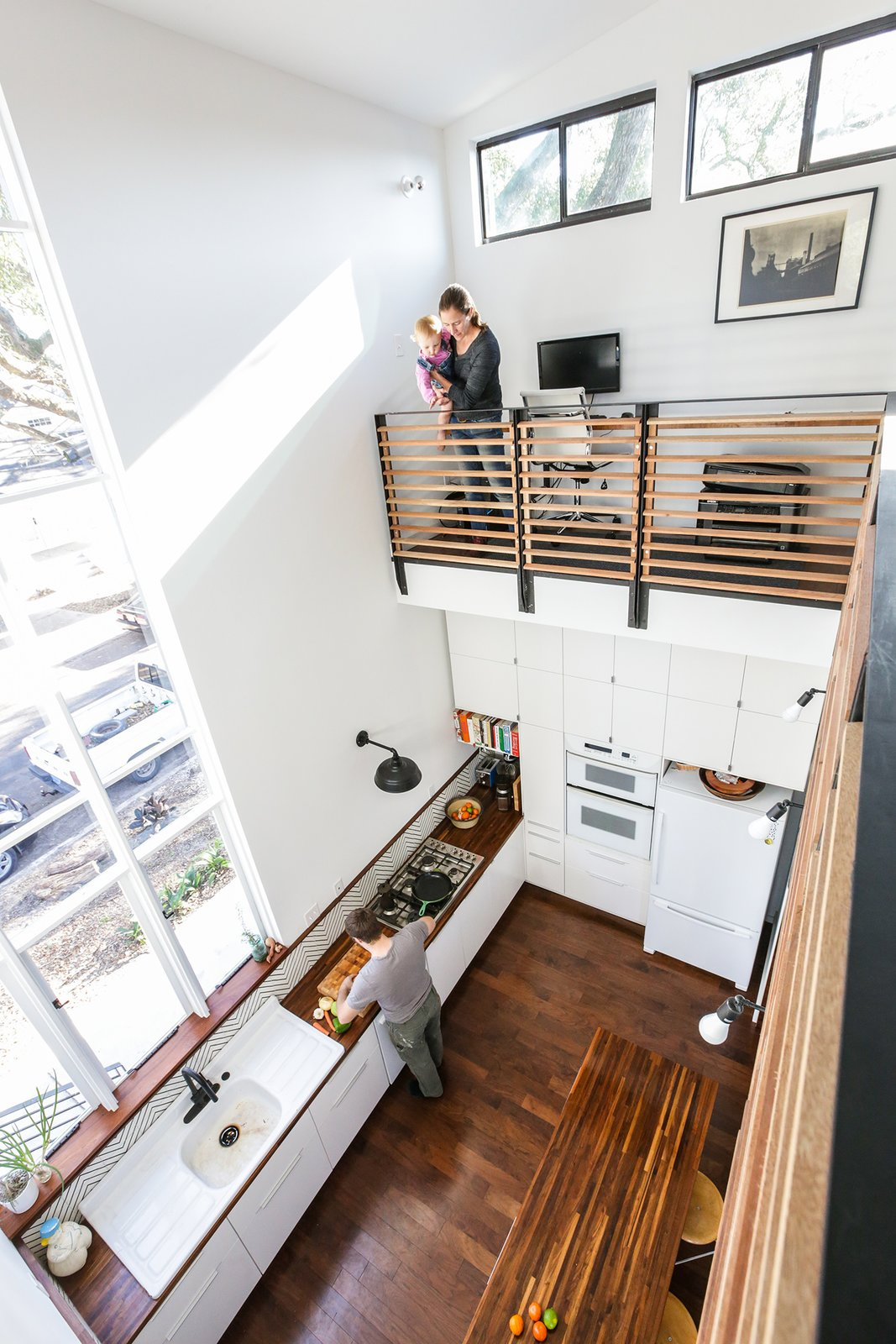 Kitchen, Wood Counter, Dark Hardwood Floor, White Cabinet, Ceramic Tile Backsplashe, Wall Oven, Refrigerator, and Drop In Sink The double height interior space overlooks the kitchen. A large custom operable assembly of windows frames views to the Oak lined street.   Dorgenois