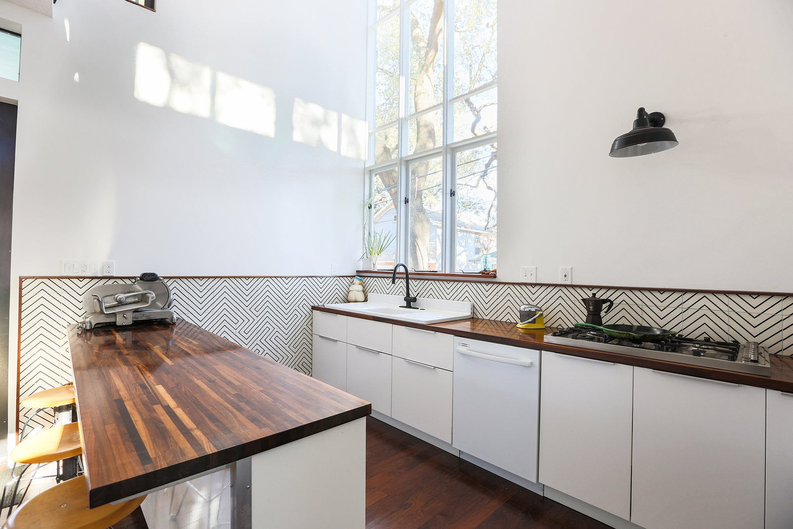 Kitchen, Wood Counter, White Cabinet, Dark Hardwood Floor, Ceramic Tile Backsplashe, Wall Lighting, Drop In Sink, and Dishwasher The light-filled kitchen space. Cle tiles are used as backsplash, Ikea cabinets and Walnut butcher-block countertops make the working surfaces of the space.   Dorgenois