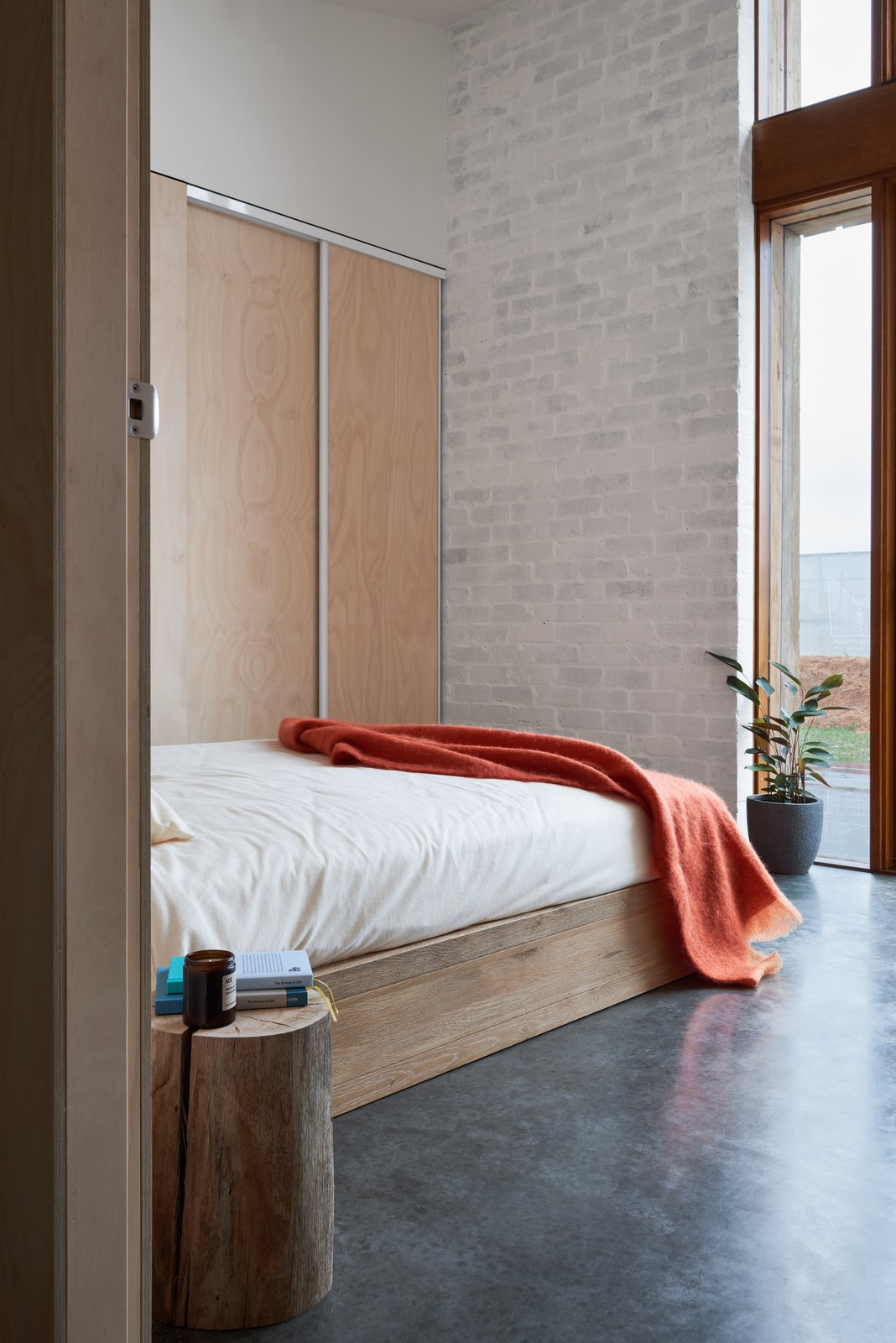 Bedroom, Night Stands, Wardrobe, Ceiling Lighting, Bed, Wall Lighting, and Concrete Floor Looking into the second bedroom featuring the home's recycled brick walls with a light natural, no VOC coat of paint.  The 10 Star Home by The Sociable Weaver