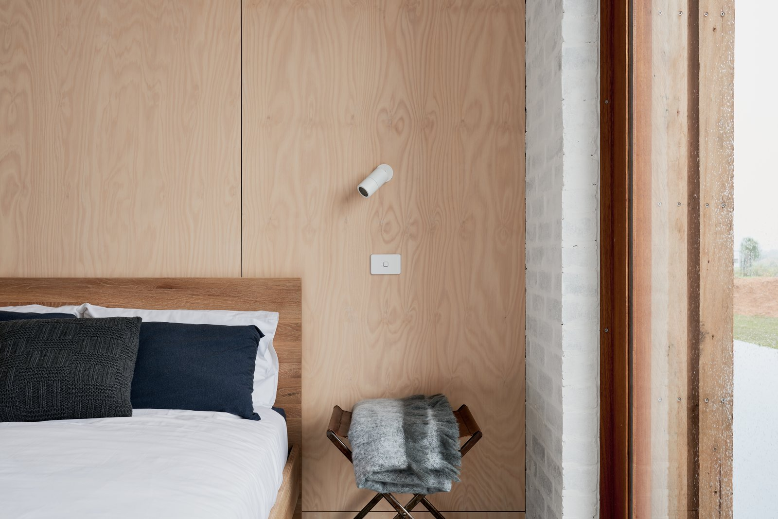 Bedroom, Bed, Chair, Ceiling Lighting, Night Stands, Wall Lighting, Accent Lighting, and Concrete Floor Main bedroom featuring recycled brick walls and sustainable, non-toxic plywood panelling. Sustainable timber bed by Totem Road.  The 10 Star Home by The Sociable Weaver
