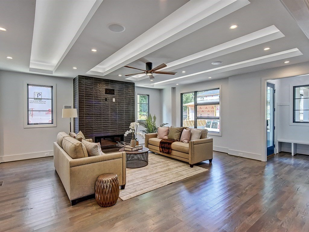 Living Room, Recessed Lighting, Ceiling Lighting, Sofa, Accent Lighting, Light Hardwood Floor, Standard Layout Fireplace, and Gas Burning Fireplace Living room with linear tray ceilings with LED uplighting. Modern fireplace with stacked tile surround.  Contemporary Craftsman Home