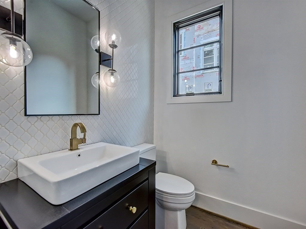 Bath Room, Light Hardwood Floor, One Piece Toilet, Ceramic Tile Wall, and Vessel Sink Powder room with accent wall  Contemporary Craftsman Home
