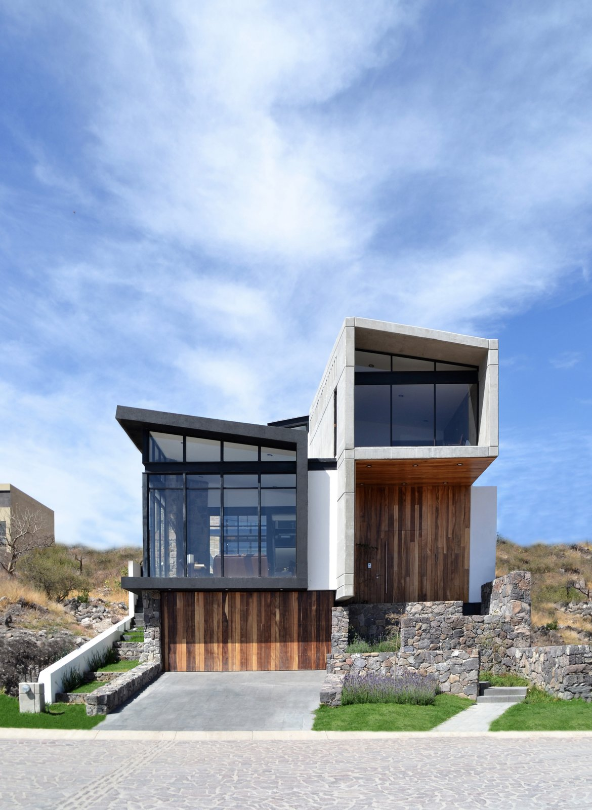 Outdoor, Front Yard, Horizontal Fences, Wall, Slope, Grass, and Landscape Lighting East Facade  Casa AB by e|arquitectos