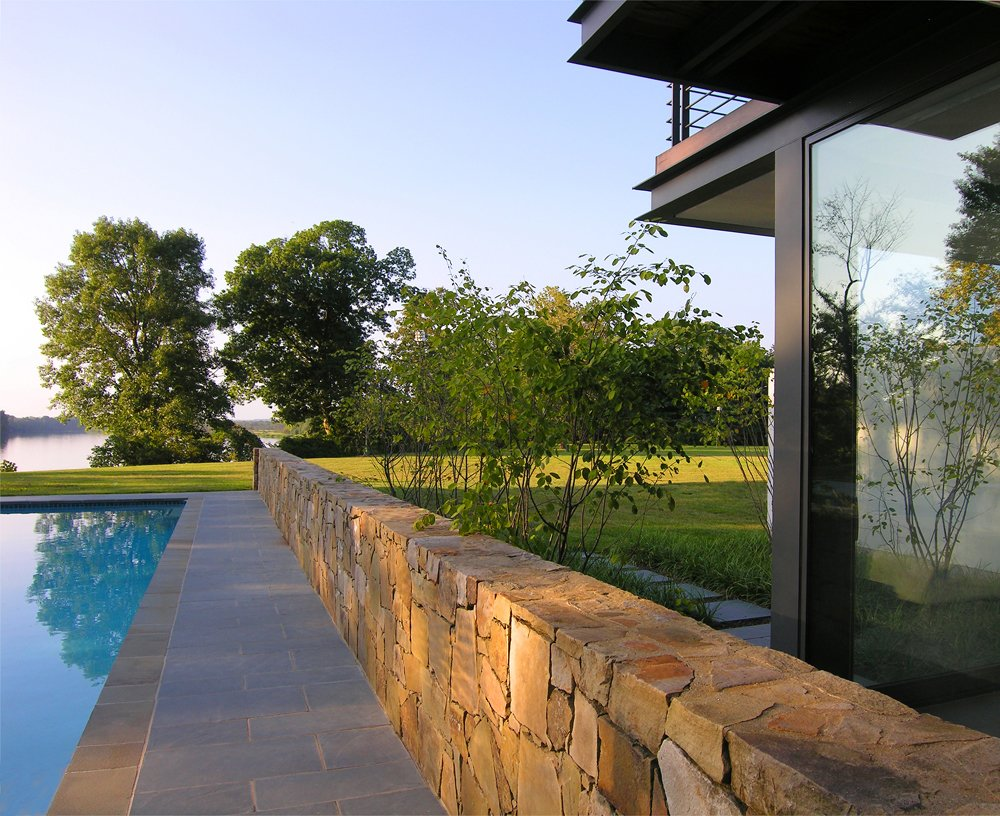 Outdoor, Garden, Back Yard, Small Pools, Tubs, Shower, Large Pools, Tubs, Shower, Plunge Pools, Tubs, Shower, Small Patio, Porch, Deck, Swimming Pools, Tubs, Shower, Decking Patio, Porch, Deck, Large Patio, Porch, Deck, Hardscapes, Gardens, and Walkways The pool house is nestled around an existing stone wall that directs the view out toward the river.  A Summer House