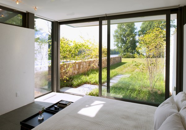 Bed, Ceiling Lighting, Windows, Limestone Floor, Metal, Picture Window Type, and Sliding Window Type A guest suite with bath and changing areas has a large sliding door out to a private garden.  A Summer House
