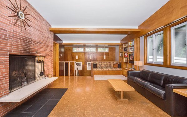 Living Room, Bookcase, Ceiling Lighting, Track Lighting, Accent Lighting, Bench, Cork Floor, and Wood Burning Fireplace Living Room  Classic Mid Century Modern home for sale