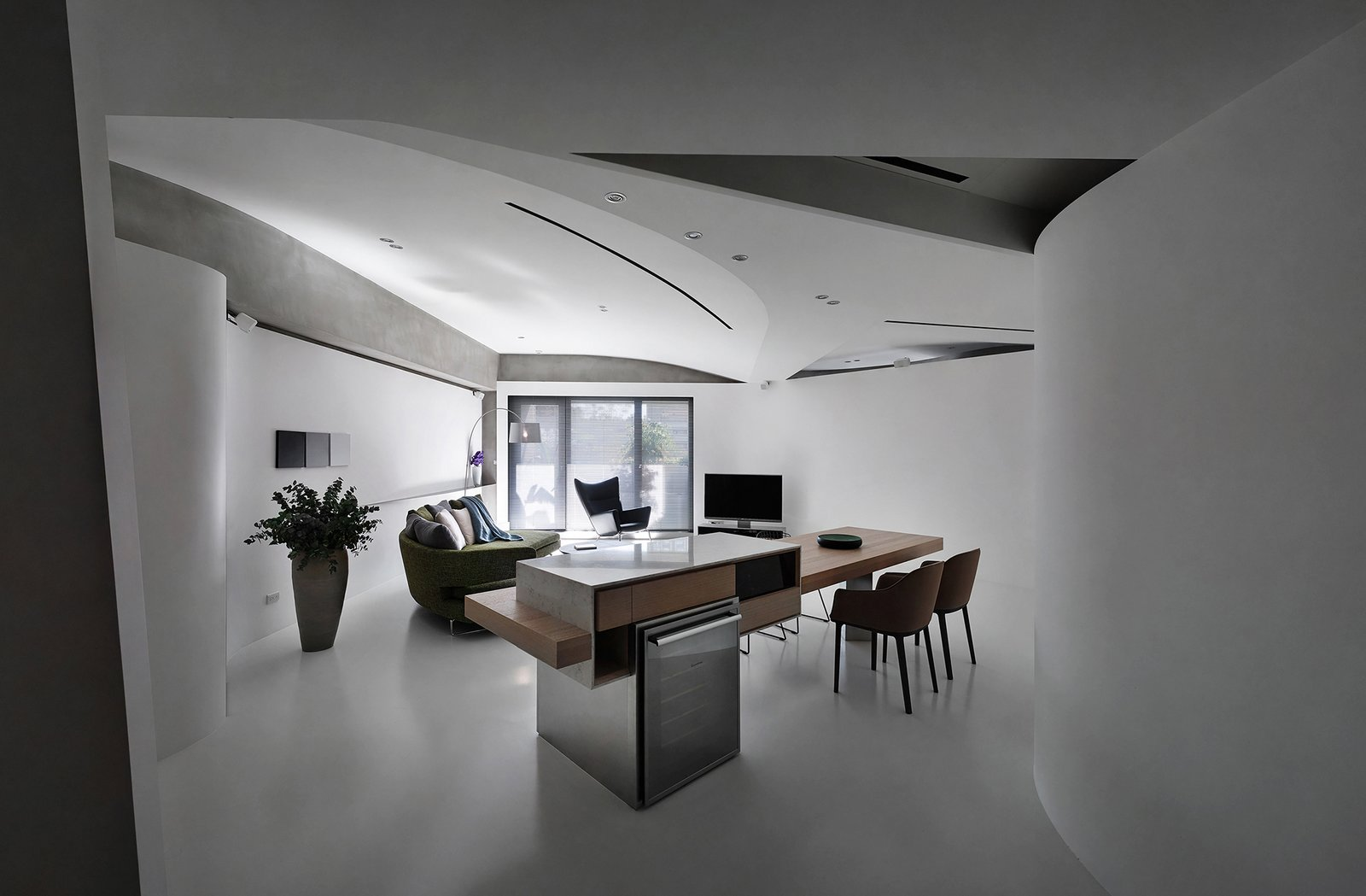 Living Room, Bar, Table, Chair, Sofa, Wall Lighting, Ceiling Lighting, Lamps, and Concrete Floor When entering the house, one could easily perceive its fluidity at the first glance.  Fluid House