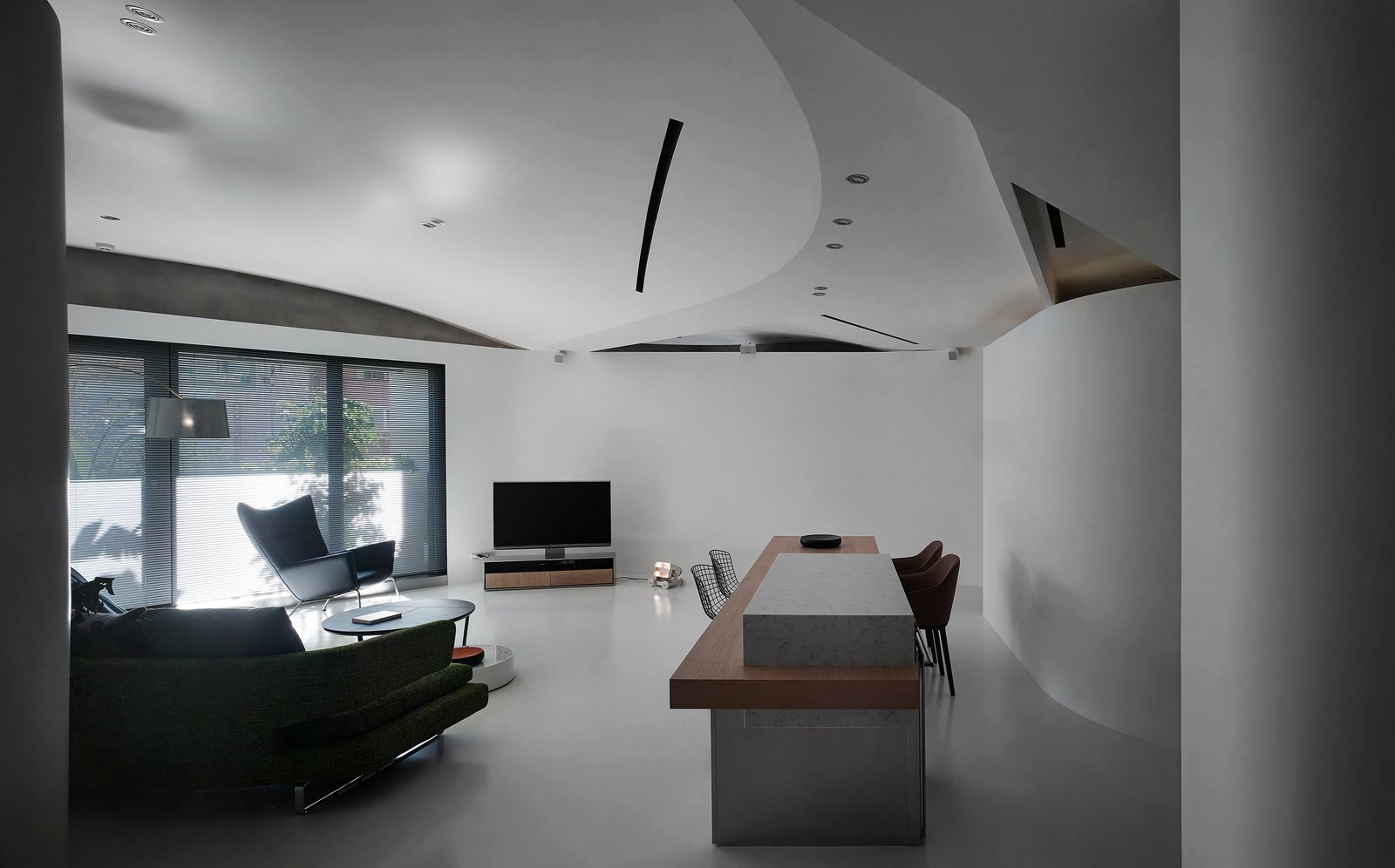Living Room, Chair, Sofa, Bar, Table, Lamps, Ceiling Lighting, Wall Lighting, and Concrete Floor The ceiling is a composite of several curved surfaces, the seams of which implicitly implying the activities underneath.   Fluid House